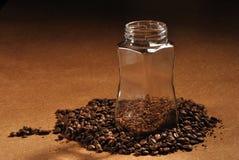 Fotografia kawowe fasole i szklany słój z natychmiastową kawą na brown tle Fotografia Stock
