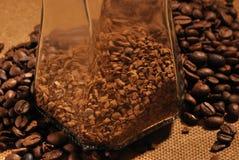 Fotografia kawowe fasole i szklany słój z natychmiastową kawą na brown tle Obrazy Stock