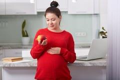 Fotografia kobieta w ciąży je owoc bogacić witaminy, ubierać w czerwonym pulowerze, spojrzenia przy wyśmienicie jabłkiem, stojaki fotografia stock
