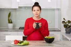 Fotografia kobieta w ciąży pije gorącego napój podczas kolacji, chwyta kubek w rękach, je wyśmienicie vegeterian sałatki, jest ub zdjęcia stock