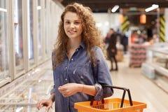 Fotografia kobieta z kędzierzawym włosy i atrakcyjnym spojrzeniem, chwyty shooping furę, kupuje produkty w supermarkecie, szuka d Zdjęcie Royalty Free