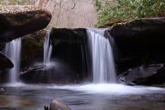 Fotografia lenta da cachoeira da velocidade do obturador de um rio pequeno da água fresca nas madeiras da montanha fotografia de stock royalty free