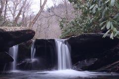 Fotografia lenta da velocidade do obturador de um rio pequeno da cachoeira com a pedra no parque das madeiras imagens de stock royalty free