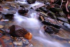 Fotografia lenta da velocidade do obturador de um rio pequeno com as rochas nas madeiras do parque das montanhas foto de stock royalty free