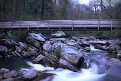 Fotografia lenta do movimento da velocidade do obturador de uma ponte de madeira sobre uma cachoeira de pressa imagem de stock