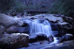 Fotografia lenta do rio da velocidade do obturador de uma cachoeira pequena sobre pedras lisas fotografia de stock royalty free