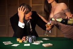 Fotografia mężczyzna emocjonalny nieudacznik w grzebaku i damach nalewa on szkło zdjęcie royalty free