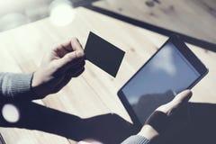 Fotografia mężczyzna Pokazuje Pustą Czarną wizytówkę, Trzyma ręki Cyfrowego Nowożytną pastylkę Drewno stołu Zamazany tło Mockup Obraz Stock