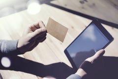Fotografia mężczyzna Pokazuje Pustą rzemiosło wizytówkę, Trzyma ręki Cyfrowego Nowożytną pastylkę Drewno stołu Zamazany tło Mocku Zdjęcie Stock