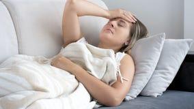Fotografia młoda kobieta z migreny lying on the beach na kanapie w domu zdjęcia stock