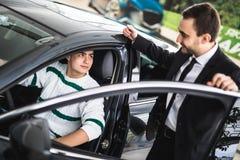 Fotografia młody męski konsultant i nabywca w nowym samochodzie w auto przedstawieniu Pojęcie dla samochodowego wynajem zdjęcia stock