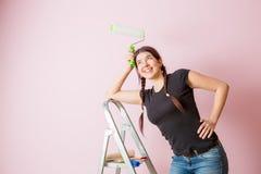 Fotografia młoda kobieta z farba rolownikiem stoi blisko schody Zdjęcia Stock
