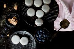 Fotografia monocromática escura O cinza endurece bolinhos de amêndoa na superfície escura da tabela, ao lado de uma colher e de u Fotos de Stock Royalty Free