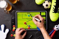 Fotografia na górze dwa kubków piankowaty piwo, stołowy futbol i istot ludzkich ręki rysuje plan, obraz royalty free