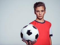 Fotografia nastoletnia chłopiec w sportswear mienia piłki nożnej piłce fotografia stock