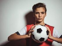 Fotografia nastoletnia chłopiec w sportswear mienia piłki nożnej piłce zdjęcie stock