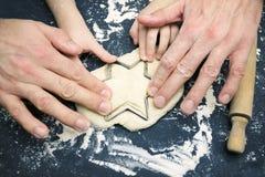 Fotografia od above ojciec i dziecko wręcza ciąć gwiazdę z ciastko krajaczem na drewnianym stole Zasięrzutna fotografia fathe fotografia stock