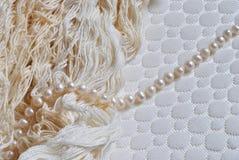 Fotografia perła sznurek i nici na białej tkaninie textured tło Obraz Stock