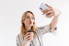 Fotografia pi?kna blondynki kobieta jest ubranym szk?a bierze selfie fotografi? na smartphone obraz stock