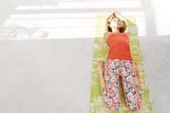 Fotografia pi?kny m?odej kobiety lying on the beach na joga macie, odpoczywaj?cy ?wiczy, k?amaj?cy w Savasana po robi? joga obraz stock