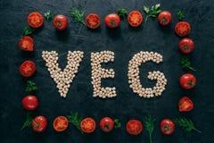 Fotografia pomidory rama i chickpea pisze list znaczenia veg Organicznie ziarna wśrodku warzywo ramy odizolowywającej nad ciemnym obraz stock