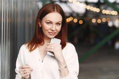 Fotografia pomyślny żeński biznesowy pracownik przerwę po pracy, wysyła wiadomości tekstowe, trzyma telefon komórkowego w ręce, u fotografia stock