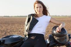 Fotografia poważny dobry przyglądający fachowy żeński rowerzysta ubierający w białej t koszula i czarnych spodniach, skórzaną kur zdjęcie stock
