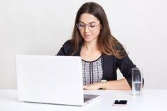 Fotografia poważny piękny copywriter w czerni ubraniach, używa laptop dla pracy i online komunikacja, siedzi przy białym biurkiem zdjęcia royalty free