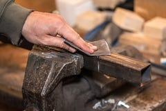 Fotografia pracownik ręka używać szklaka na metalu workpiece Zdjęcia Stock