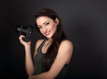 Fotografia profissional fêmea nova de sorriso que guarda o camer da foto fotografia de stock