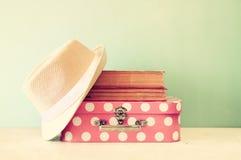 Fotografia różowa walizka z polek kropkami, fedora kapeluszem i stertą książki, obraz royalty free
