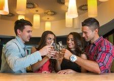 Fotografia radośni przyjaciele komunikuje z each inny w barze Zdjęcia Stock