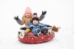 Fotografia rozochocony dziewczyny i chłopiec jeździecki tubing zdjęcia royalty free