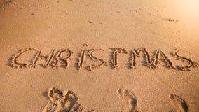 Fotografia słów boże narodzenia pisać na piasek plaży przy oceanem Pojęcie wakacje, nowy rok i turystyka zimy, fotografia stock