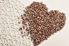 Fotografia serce kształtował kawowe fasole na beżowym tle Fotografia Stock