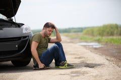 Fotografia sfrustowany mężczyzna obsiadanie obok łamanego samochodu z otwartym kapiszonem obrazy royalty free