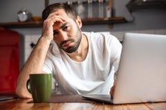 Fotografia sfrustowany mężczyzna używa srebnego laptop przy stołem w nowożytnym mieszkaniu podczas gdy siedzący obraz stock