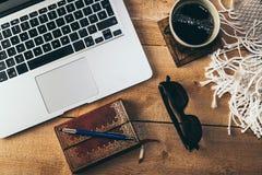 Fotografia superior de um portátil, de um caderno, de óculos de sol e de uma xícara de café foto de stock