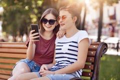 Fotografia szczęśliwa nastoletniej dziewczyny wiadomość w ogólnospołecznych sieciach, używa mądrze telefon dla rozrywki, jest ubr zdjęcie royalty free