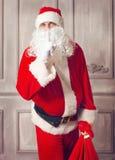 Fotografia szczęśliwy Święty Mikołaj patrzeje c z dużą torbą teraźniejszość Zdjęcia Royalty Free