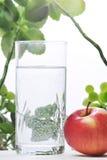 Fotografia szkło woda i jabłko w nim z niektóre zielonymi roślinami, biały odosobniony tło Zdjęcia Stock