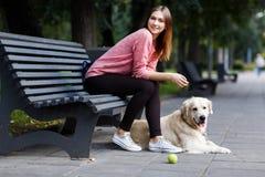 Fotografia uśmiechnięty dziewczyny obsiadanie na ławce, psi aporter Obraz Royalty Free