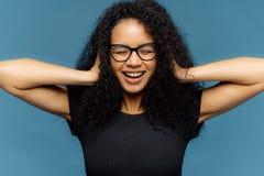 Fotografia urocza uśmiechnięta Afro kobieta z crsip włosy, pokrywa ucho, być w dobrym nastroju, jest ubranym przypadkową czerni t obraz stock