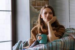 Fotografia w domowej atmosferze młody piękny dziewczyny obsiadanie Zdjęcie Stock