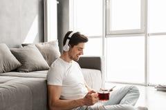 Fotografia w profilu słucha muzyka na smartphone w młody facet fotografia stock
