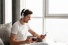 Fotografia w profilu słucha muzyka na telefonie komórkowym uśmiechnięty facet zdjęcie stock
