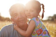 Fotografia zadowolony mały dzieciak obejmuje ona marszczył dojrzałego dziadu, odczucie miłość each inny, poza przeciw światła sło obraz stock
