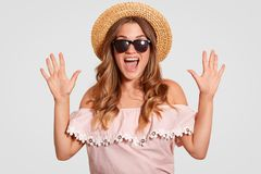 Fotografia zadziwiająca atrakcyjna kobieta z rozradowanym wyrażeniem, reaguje na coś cudownym, utrzymanie ręki podnosić, krzyczy  zdjęcia stock