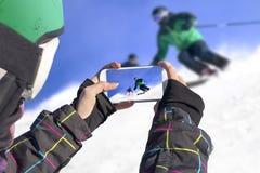 Fotografiado dos esquiadores con el teléfono celular Foto de archivo