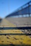 Fotografiado a la hora de la puesta del sol con la reflexión de una cerca en el puente Varadin de la cinta amarilla en la acera s Fotos de archivo